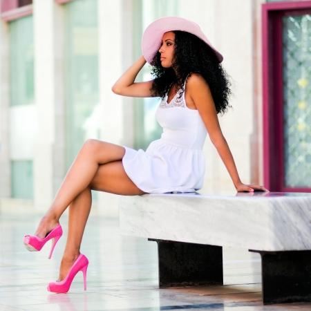 African American: Retrato de una mujer joven negro, modelo de la moda con un vestido y un sombrero de sol, con el peinado afro en el medio urbano