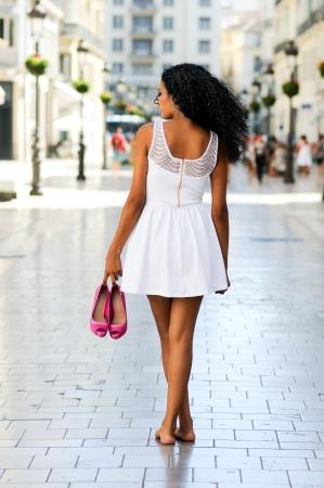 Retrato de una mujer joven negro, afro peinado, caminar descalzo en una calle comercial Foto de archivo - 16653407