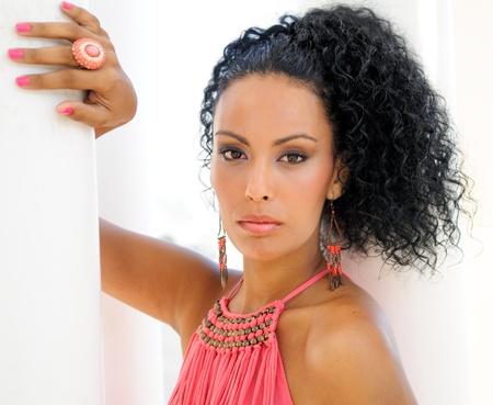 aretes: Retrato de una mujer joven negro, modelo de la moda, con un vestido rosa y aretes peinado afro
