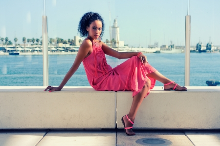Portrait of a young black woman, afro hairstyle, wearing long pink dress, in the harbour photo