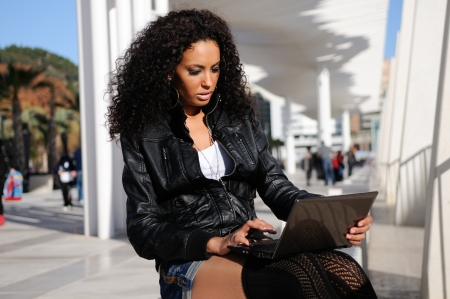 mixed race people: Happy relaxed african girl using a laptop in the street  Stock Photo