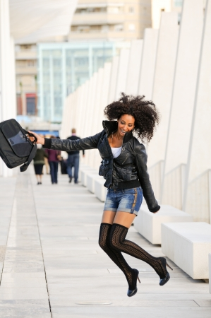 Young pretty black woman jumping in the street with a briefcase