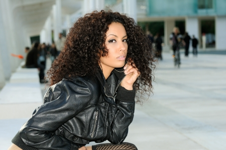 Funny black female model at fashion sitting on a bench photo