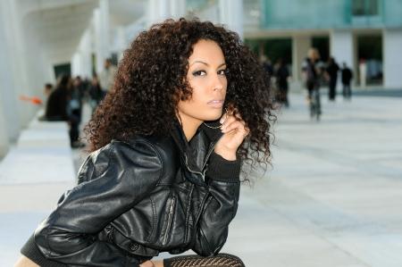 Modelo femenino negro divertido en la moda que se sienta en un banco Foto de archivo - 16653622