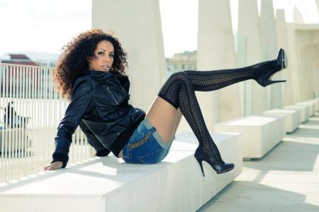 tacones negros: Divertido modelo femenino negro en la moda con zapatos de tacón alto sentado en un banco