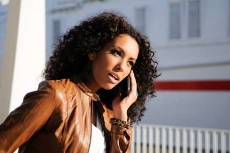 afro hair: Portrait of pretty blak woman in urban background talking on phone  Stock Photo
