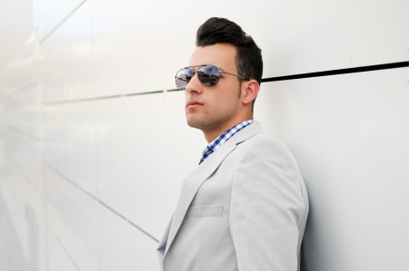 Portrait of a young handsome man, model of fashion, wearing tinted sunglasses photo