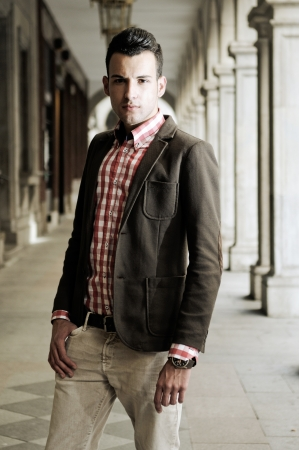 Portrait of a young handsome man, model of fashion, wearing jacket and shirt in urban background photo