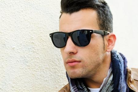 Retrato de un hombre joven y guapo, modelo de moda, gafas de sol polarizados en fondo urbano Foto de archivo - 16753428