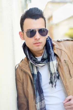 Portrait of a young handsome man, model of fashion, wearing tinted sunglasses in urban background photo