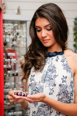Portrait of attractive young woman buying a bracelet at a jewelry Stock Photo - 16753361