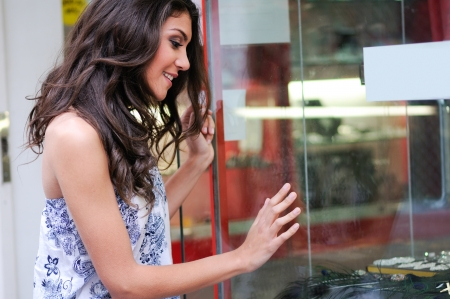 Portrait of an attractive young woman looking at the shop window  Stock fotó