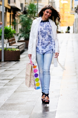Portrait of a beautiful woman with shopping bags walking along a commercial street Stock Photo - 16753444