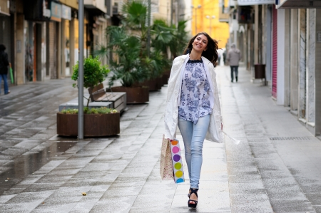 Portrait of a beautiful woman with shopping bags walking along a commercial street Stock Photo - 16753383