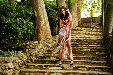 Portrait of a beautiful young woman, model of fashion, in a garden stairs  photo