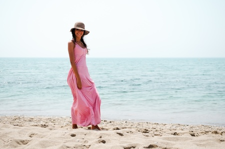 Portrait of a beautiful woman with long pink dress on a tropical beach  photo