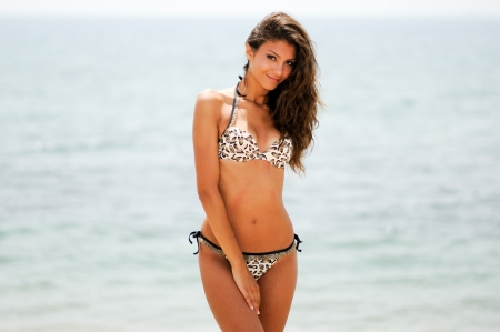 Portrait of a woman with beautiful body on a tropical beach, wearing a bikini photo
