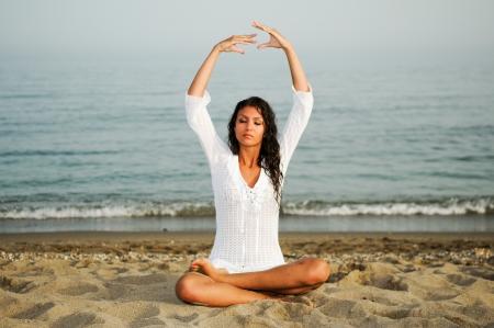 Pretty woman doing yoga on the beach  Stock Photo