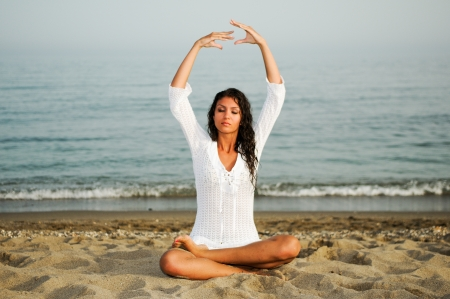 Pretty woman doing yoga on the beach  photo