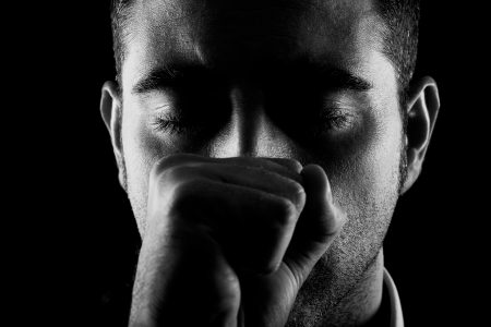 eye's closed: Portrait of a man with fist and eyes closed on black background Stock Photo