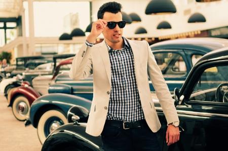 moda: Retrato de un hombre joven y guapo, modelo de moda, chaqueta de vestir y camisa con los coches viejos Foto de archivo