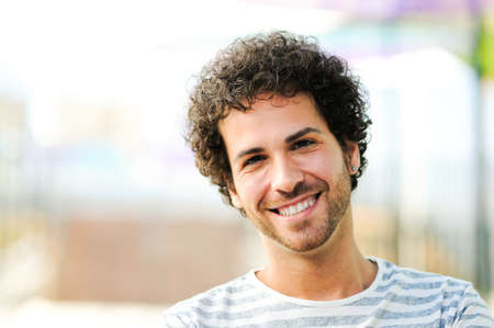 Portrait of handsome man with curly hairstyle smiling in urban background