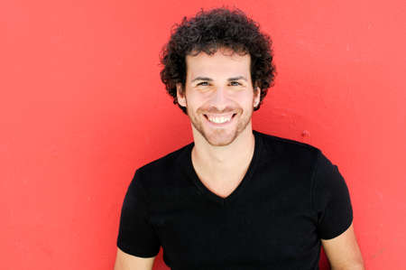 Portrait of handsome man with curly hairstyle smiling in urban background photo
