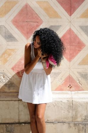 vistiendose: Retrato de una mujer joven negro, peinado afro, vestirse en la calle