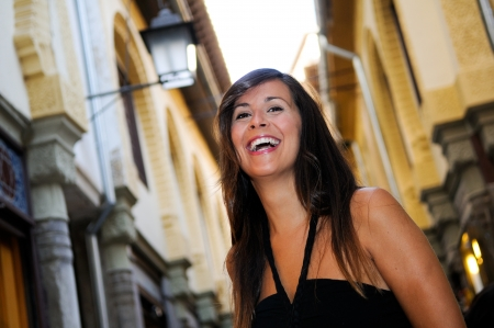 citylife: Portrait of an attractive smiling woman in urban background