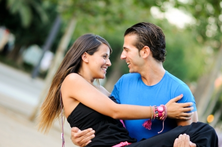 carrying girlfriend: Portrait of love couple embracing outdoor in park looking happy