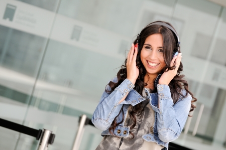 Young girl with headphones listening to the music and dancing in the street  photo
