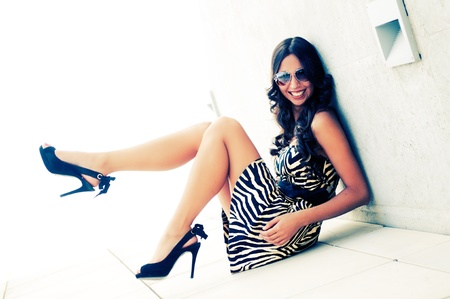 Funny female model at fashion with high heels sitting on the floor photo