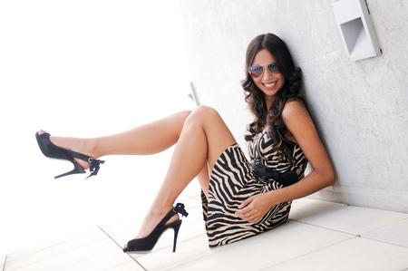poses de modelos: Divertido modelo femenina en la moda con zapatos de tacón alto sentado en el suelo