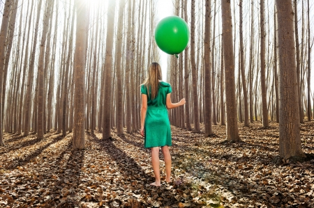 flotation: Beautiful blonde girl, dressed in green, standing in the forest