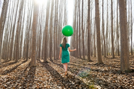 flotation: Beautiful blonde girl, dressed in green, walking into the forest