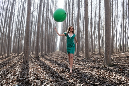 Beautiful blonde girl, dressed in green, walking into the forest photo