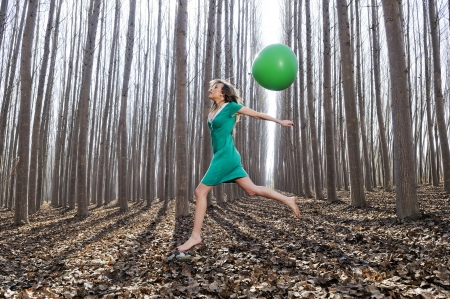 latex girl: Beautiful blonde girl, dressed in green, jumping into the woods with a balloon in Fuente Vaqueros, Granada, Spain