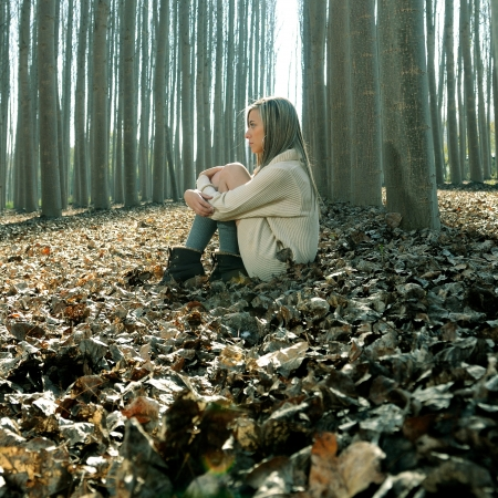 poplars: Beautiful blonde sitting on leaves in a forest of poplars