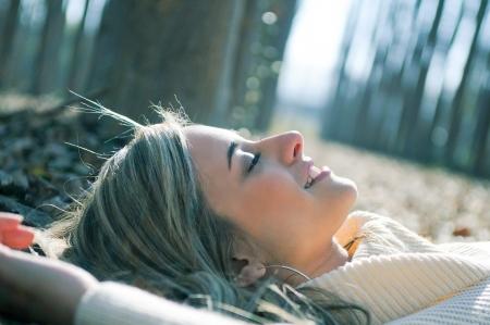 poplars: Smiling blonde girl lying on leaves in a forest of poplars