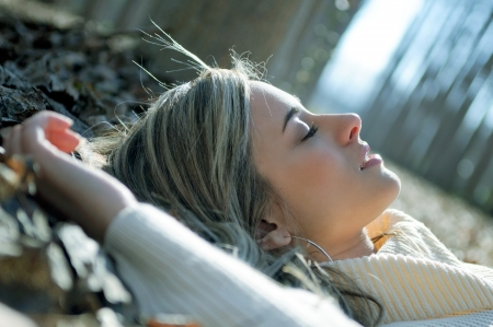 poplars: Beautiful blonde girl lying on leaves in a forest of poplars Stock Photo