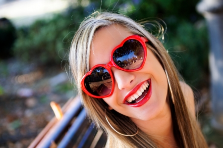 Funny girl with red heart glasses in a park photo