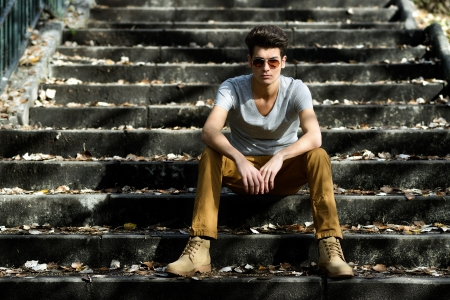Portrait of a young handsome man, model of fashion, with toupee in stairs Stock Photo