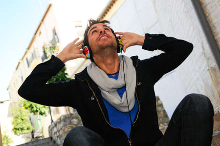 estilo urbano: Retrato de hombre atractivo en fondo urbano de escuchar la m�sica