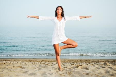 Mujer bonita que hace yoga en la playa Foto de archivo - 17645330