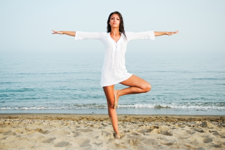 Pretty woman doing yoga on the beach  Stock Photo