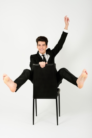 Portrait of a happy young businessman sitting in a chair with raised arm, on white background  photo