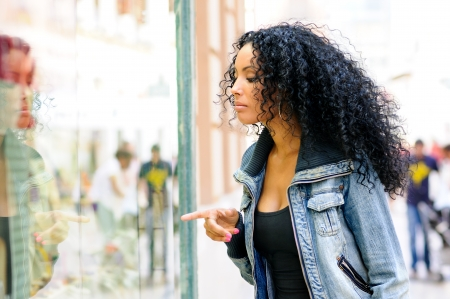 Portrait of an attractive black woman, afro hairstyle, looking at the shop window  photo