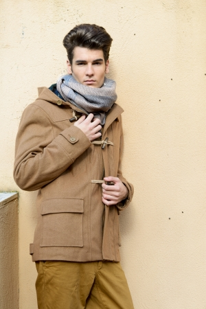 parka: Portrait of a young handsome man, model of fashion, with toupee in urban background