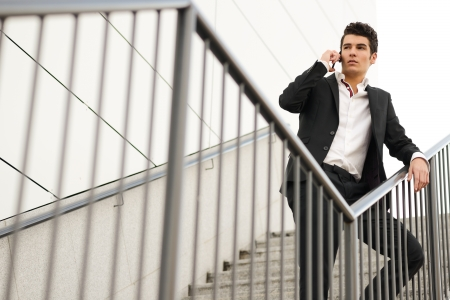 Portrait of a young businessman in an office building talking on the phone photo