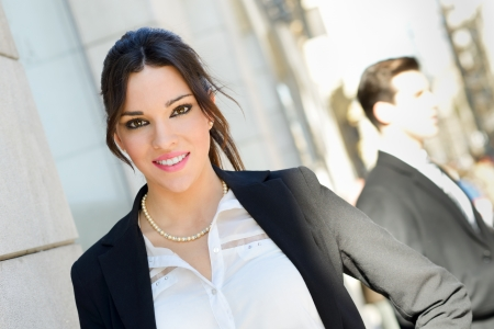company building: Portrait of an attractive businesswoman standing outside of company building  Couple working  Stock Photo